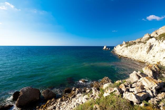 Vista do mar de águas cristalinas da costa, litoral rochoso e sol forte