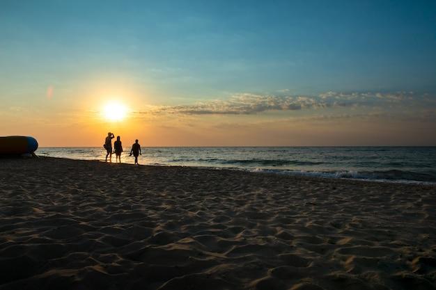 Vista do mar de manhã com três pessoas à luz de fundo.