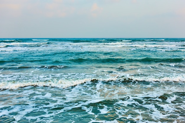 Vista do mar de ondas suaves e horizonte do mar no início da noite