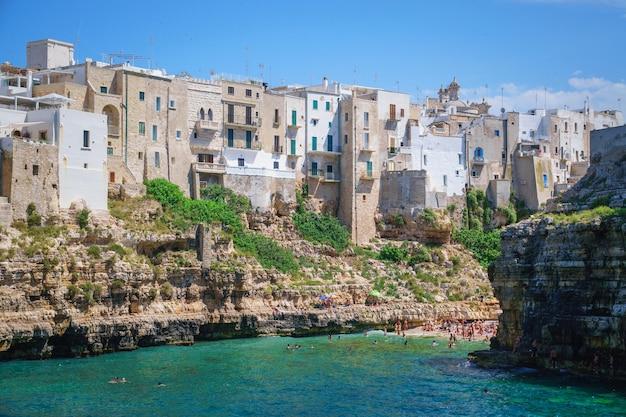 Vista do mar de polignano a mare e da praia com turistas, puglia, itália