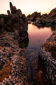 Vista do mar durante o pôr do sol ou a luz do nascer do sol da natureza. maravilhosa paisagem natural com pedras em primeiro plano bela composição da natureza.