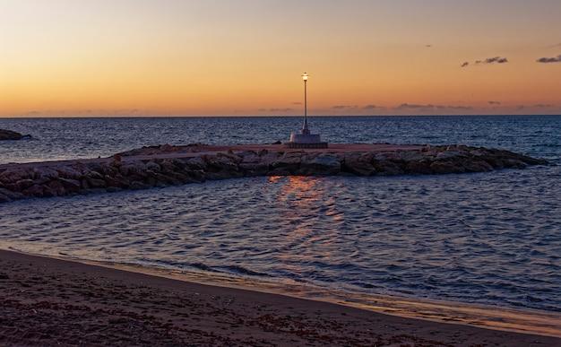 Vista do mar e poste de luz na praia de pedregalejo ao entardecer.