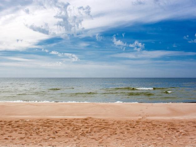 Vista do mar ensolarado com céu nublado e praia de areia