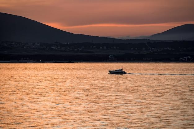 Vista do mar laranja brilhante ao pôr do sol, iate de recreio tendo como pano de fundo as montanhas da cidade turística de gelendzhik