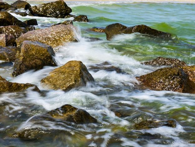 Vista do mar negro, com grandes pedras no dia ensolarado de verão