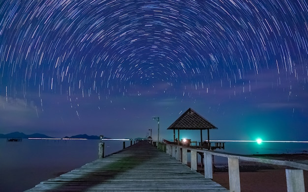 Vista do mar ponte de madeira com movimento de exposição de velocidade de céu noturno