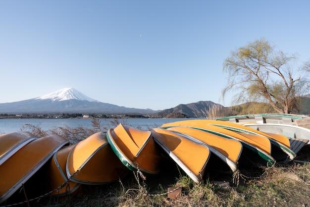Vista do monte. fuji ou fuji-san com barco amarelo e céu claro no lago kawaguchiko, japão.