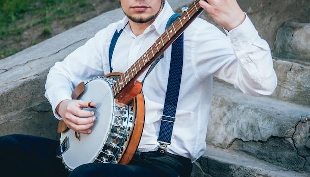Vista do músico tocando banjo na rua