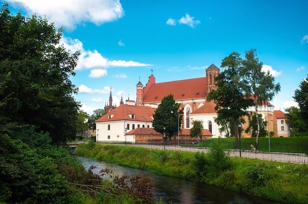 Vista do outro lado do rio para a igreja católica romana de santa ana e a igreja de são francisco e são bernardo na lituânia, vilnius,