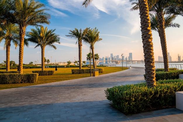 Vista do parque de abu dhabi, emirados árabes unidos. ruas mágicas de abu dhabi com edifícios altos de vidro sobre a baía.