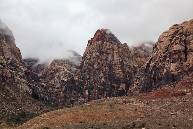 Vista do parque nacional da garganta vermelha da rocha da montanha no dia nevoento.