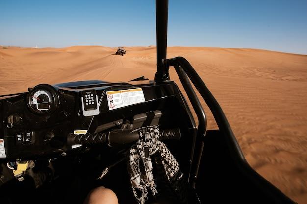 Vista do passageiro em uma moto-quatro de buggy dirigindo em um safári no deserto de dubai