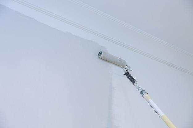 Vista do pintor pintando a parede, com rolo de pintura no espaço vazio em casa