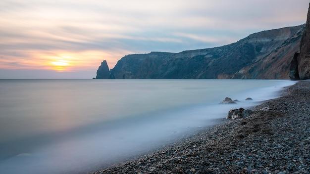 Vista do pôr do sol do mar e da praia, a rocha vulcânica da rocha é iluminada pelo pôr do sol quente, areia e seixos, basalto vulcânico como na islândia.