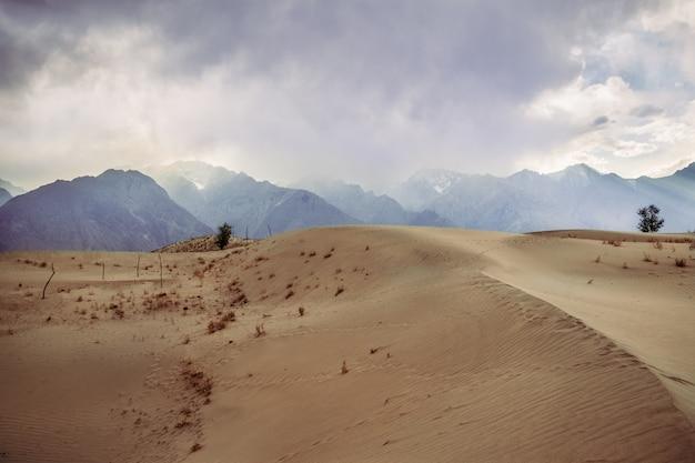 Vista do pôr do sol e céu nublado no deserto frio de katpana skardu