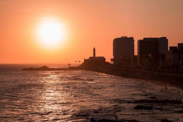 Vista do pôr do sol na barra da praia com o farol da barra ao fundo.
