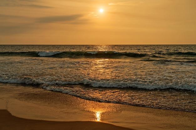 Vista do pôr do sol na praia com ondas pitorescas