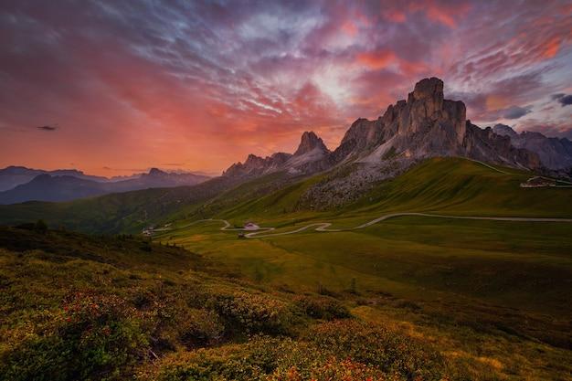 Vista do pôr do sol no verão em passo di giau com o monte ra gusela no fundo e rododendros no primeiro plano colle santa lucia dolomitas itália