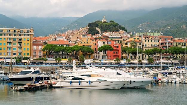 Vista do porto marítimo e da cidade barcos atracados, edifícios de iates e colinas verdes