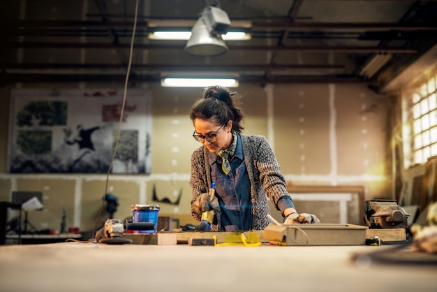 Vista do retrato da encantadora funcionária motivada sorridente com óculos, pintando madeira na oficina