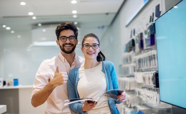 Vista do retrato da menina de estudante jovem sorridente charmosa muito animada com óculos, lendo as especificações enquanto o namorado dela ao lado dela e aparecendo o polegar