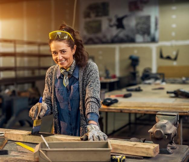 Vista do retrato de feliz atraente profissional feminino trabalhador pintura madeira com cor preta na oficina ensolarada