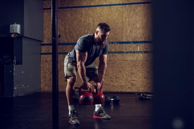 Vista do retrato de jovem barbudo focado forte forma muscular fisiculturista homem agachado com kettlebells pesados nas mãos no ginásio.