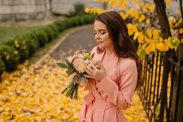 Vista do retrato de uma noiva morena jovem sensual bonita no vestido de casamento rosa e em pé no parque outono perto da catedral vintage e segurando o buquê de casamento.