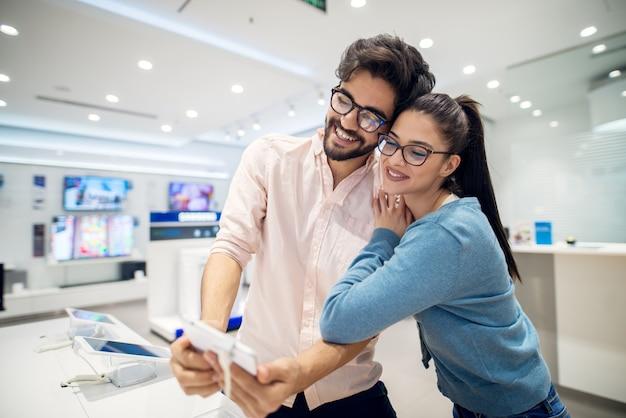 Vista do retrato do jovem casal em pé abraçado na frente da mesa com comprimidos e testando a operação de selfie na loja de tecnologia.