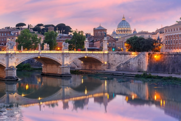 Vista do rio tibre, a ponte vittorio emanuele ii e a catedral de são pedro durante o pôr do sol em roma, itália.