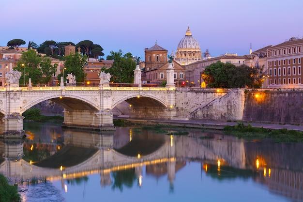 Vista do rio tibre, ponte vittorio emanuele ii e a catedral de são pedro durante a hora azul da manhã em roma, itália.