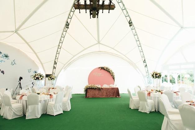 Vista do salão do casamento, mesas de casamento decoradas com flores frescas
