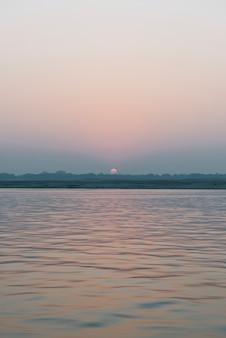 Vista do sol no rio ganges em varanasi, índia