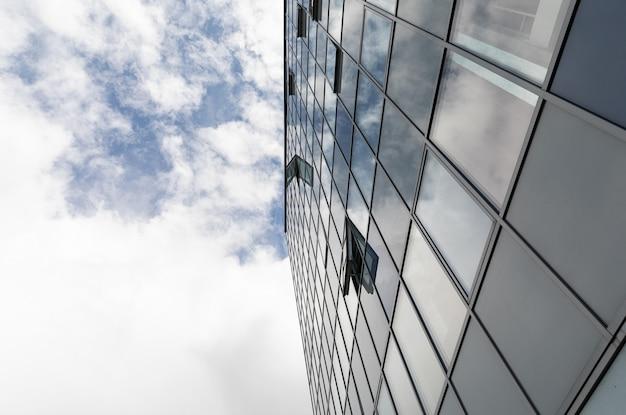 Vista do solo de nuvens no céu em dia de verão com fachada de vidro do edifício