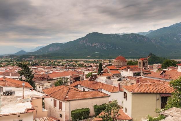 Vista do telhado de uma pequena cidade europeia com telhados vermelhos em um vale na montanha sob um céu nublado