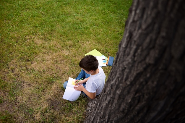 Vista do topo. aluno inteligente fazendo lição de casa, escrevendo no caderno, resolvendo tarefas matemáticas, sentado na grama verde do parque. de volta às aulas, conhecimento, ciência, educação, conceitos de aprendizagem.