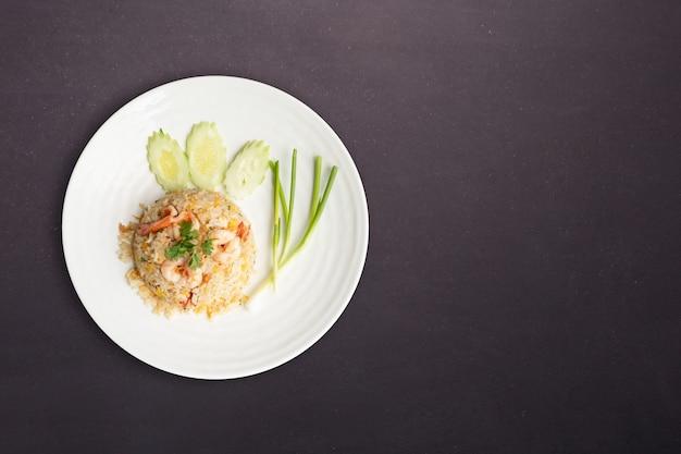 Vista do topo. arroz frito com camarão em prato redondo branco isolado no fundo preto de pedra da natureza. conceito de comida tailandesa