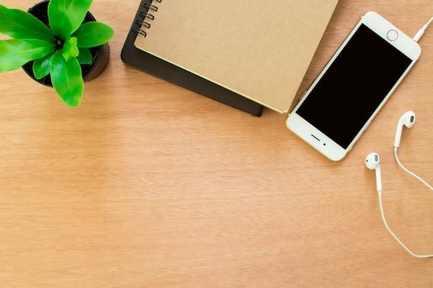 Vista do topo. caderno do telefone com um potenciômetro de flor na tabela de madeira velha. perto da janela