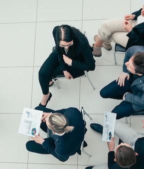 Vista do topo. colegas de trabalho apertando as mãos uns dos outros na reunião
