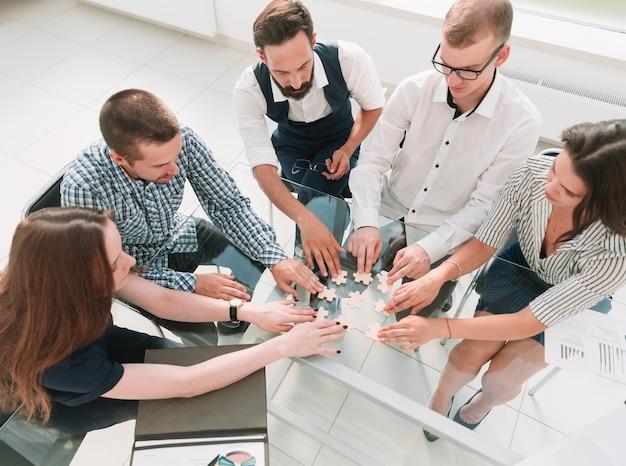 Vista do topo. colegas de trabalho coletando quebra-cabeça, sentado à mesa. conceito de negócios