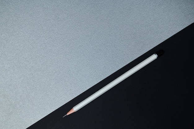 Vista do topo . composição plana lay de ferramentas de escritório. lápis cinza e parte de papel preto em um fundo cinza