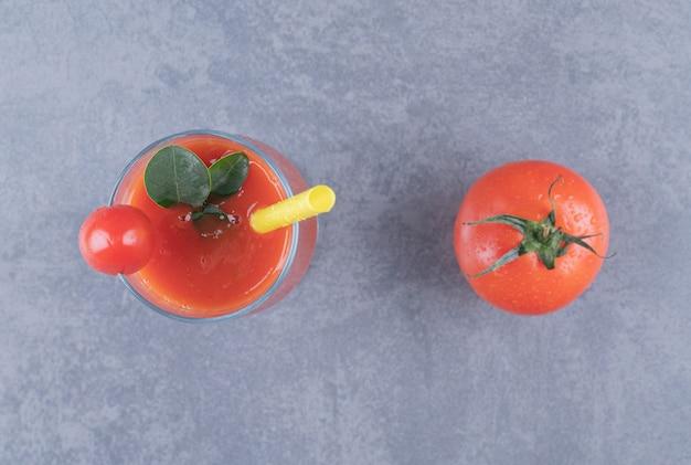 Vista do topo. copo de suco de tomate fresco e tomate em um fundo cinza.