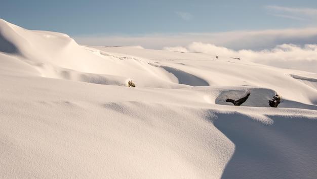 Vista do topo de uma montanha coberta de neve com um alpinista caminhando sozinho e um horizonte nublado
