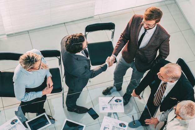 Vista do topo. empresários apertando as mãos na sala de reuniões. conceito de negócios.