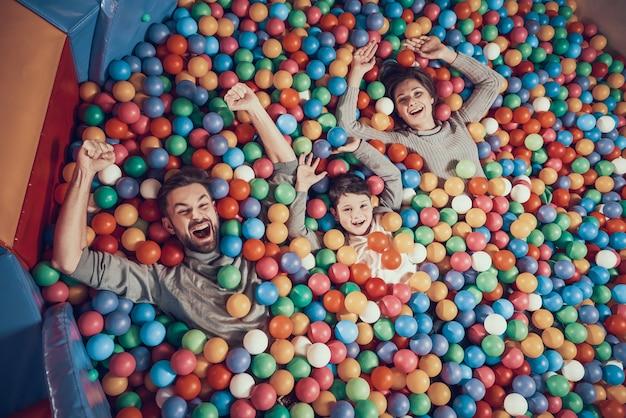 Vista do topo. família feliz, mentindo, em, piscina, com, bolas
