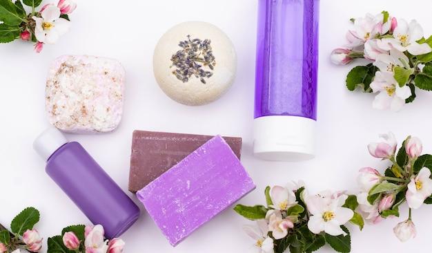 Vista do topo. frascos de cosméticos lilás, bomba de banho, sabonete artesanal, sal de banho com flores de pêra em um fundo branco. conceito de cosméticos orgânicos naturais. postura plana