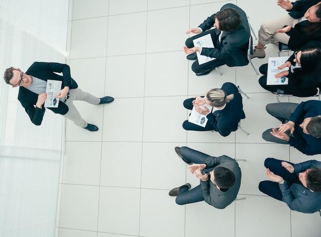 Vista do topo. gerente mostrando os resultados do crescimento financeiro em uma reunião de trabalho.