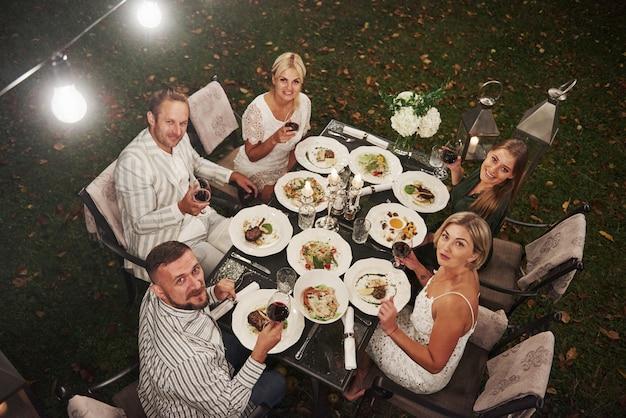 Vista do topo. grupo de amigos no desgaste elegante jantar de luxo
