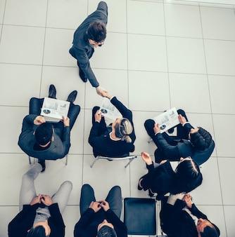 Vista do topo. grupo de trabalho discutindo uma nova estratégia em uma reunião de escritório.