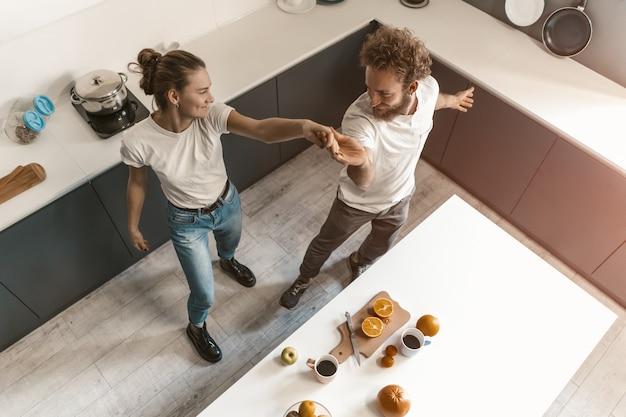 Vista do topo. jovem casal dançando na cozinha, vestindo roupas casuais, enquanto cozinhava juntos em casa, no amor, se divertindo.